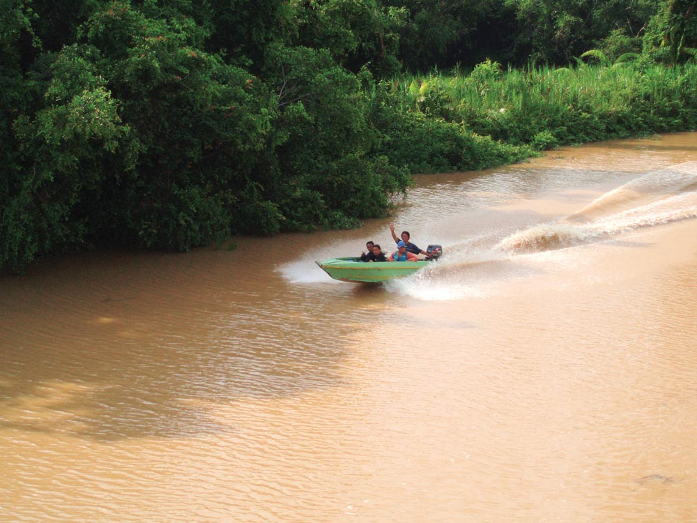 Locals on small boat greet superyacht crew on the Kinabatangan River