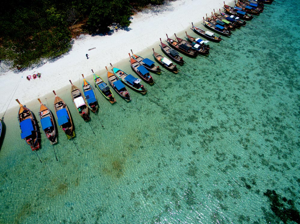 Longtail boats waiting at Koh Rawi to take guests back to Koh Lipe